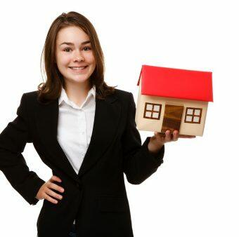 Girl holding model of house isolated on white