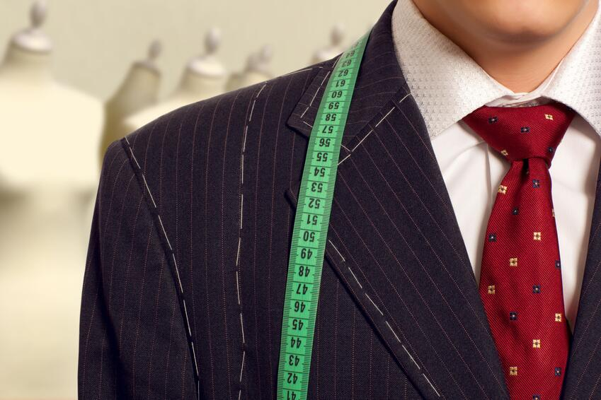 Businessman getting measured by a tailor