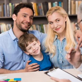 Happy family of three talking with psychologist. Psychologist taking notes. There are many books in psychologist office